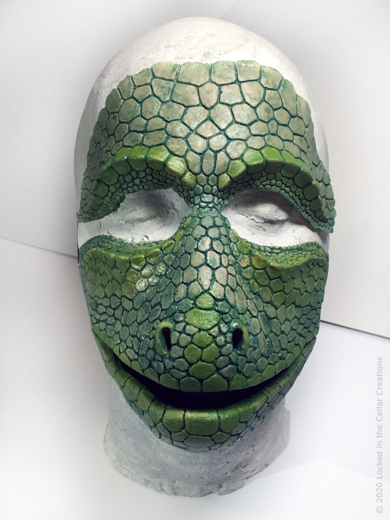 The Reptile face mask + makeup combo comes standard with black elastics on the mask that go around the head. The forehead prosthetic has to be glued on.